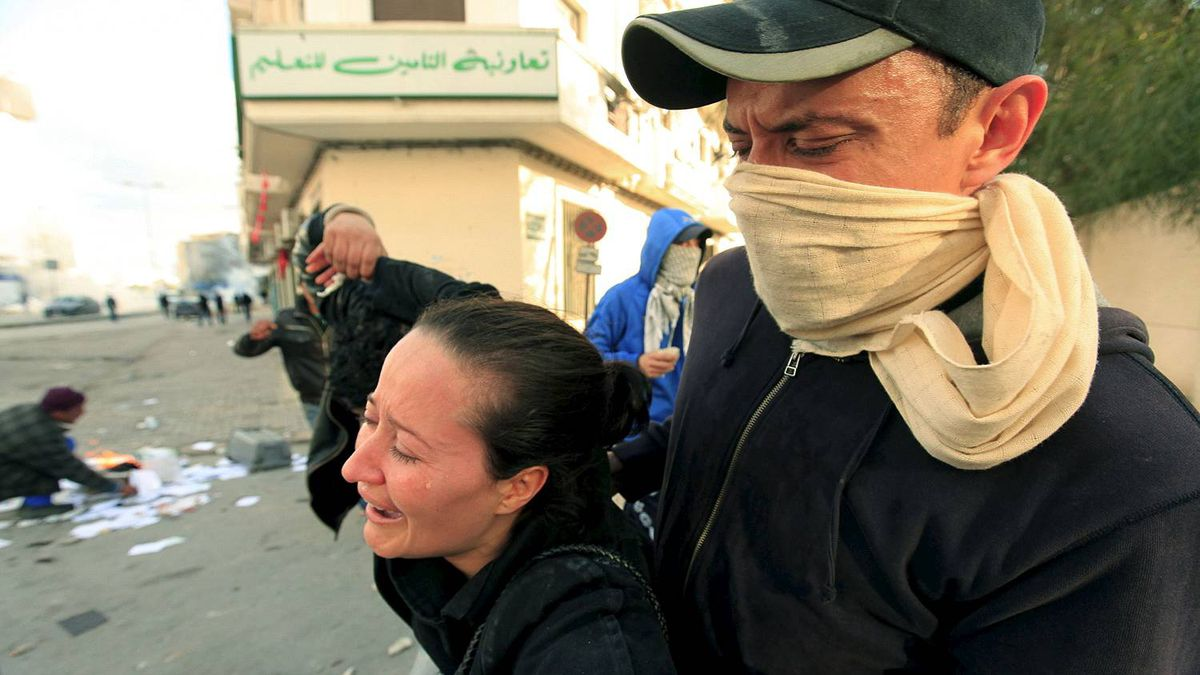 Rioters carry a crying woman during clashes with the police in the capital Tunis Jan. 14, 2011.