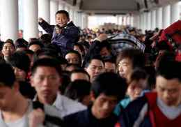 Passengers rush to board a train at the Guangzhou railway station