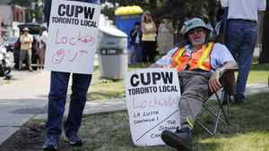 A Canadian Union of Postal Workers (CUPW) member sits in front of a Canada Post sorting facility in Toronto, June 15, 2011.