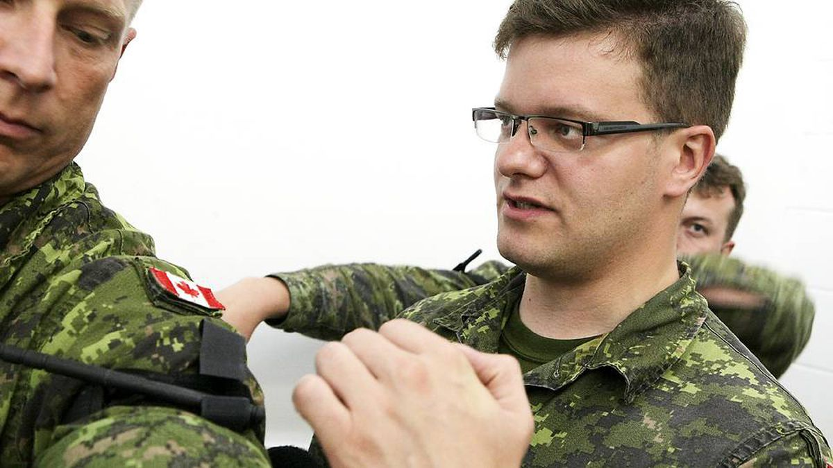 Captain Simon Mailloux, right, helps a colleague put a tourniquet on his arm during a Caring Combat Situation course at the Valcartier garrison in Quebec.