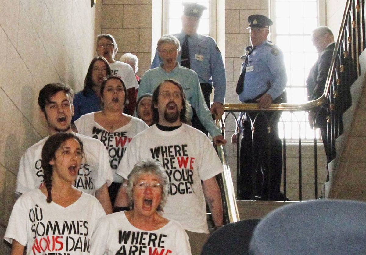 A group of chanting protesters are led away by House of Commons security after they disrupted Finance Minister Jim Flaherty.s delivery of the federal budget on Parliament Hill in Ottawa.