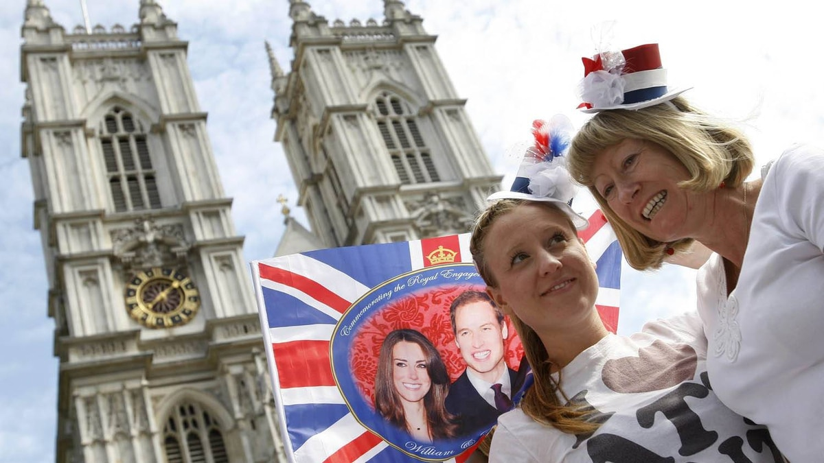 Royal fans Gemma and Jeanette Freeman from western England hold their position on the pavement near Westminster Abbey in London, Wednesday, April 27, 2011.