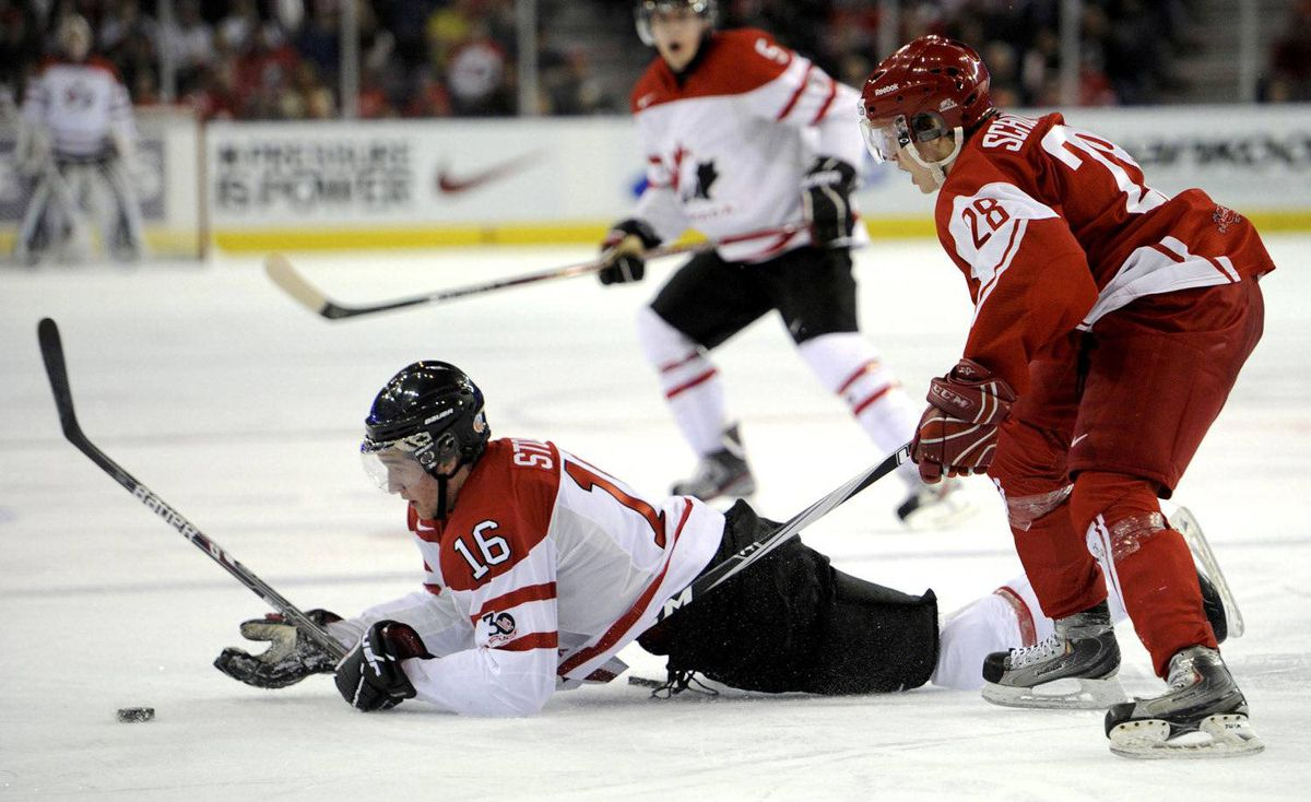 Canada's Mark Stone knocks the puck away as Denmark's Anders Schultz follows during the third period of play at the 2012 IIHF U20 World Junior Hockey Championships in Edmonton, Alberta, December 29, 2011.