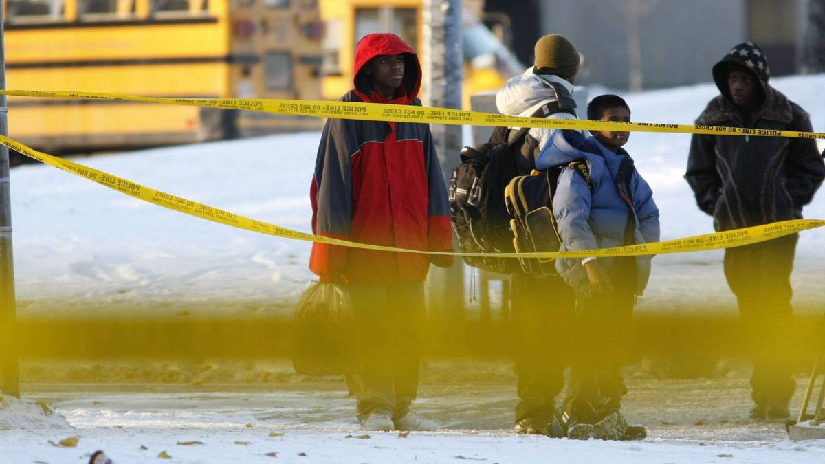 A group of students walk in front of yellow police tape after their school was reopened following a shooting at the corner of Birchmount Rd., and Bay Mills Blvd.