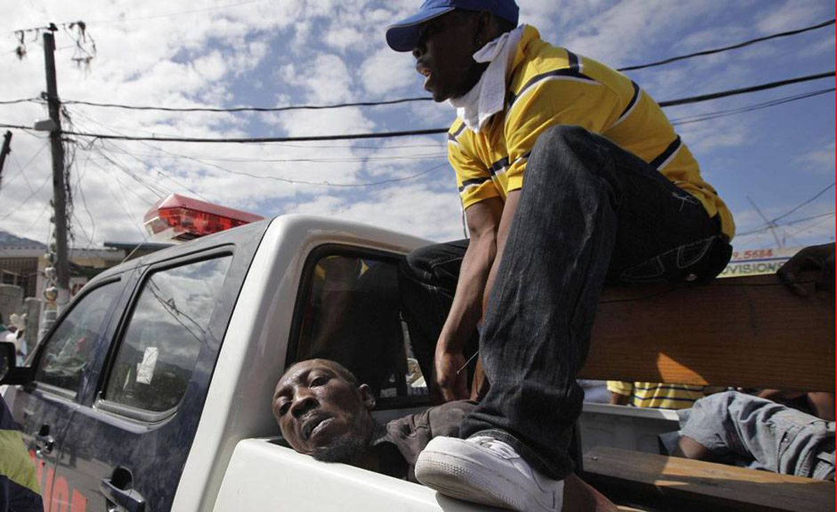 Police guards a detained man accused of trying to steal food in a market in Port-au-Prince, Thursday.