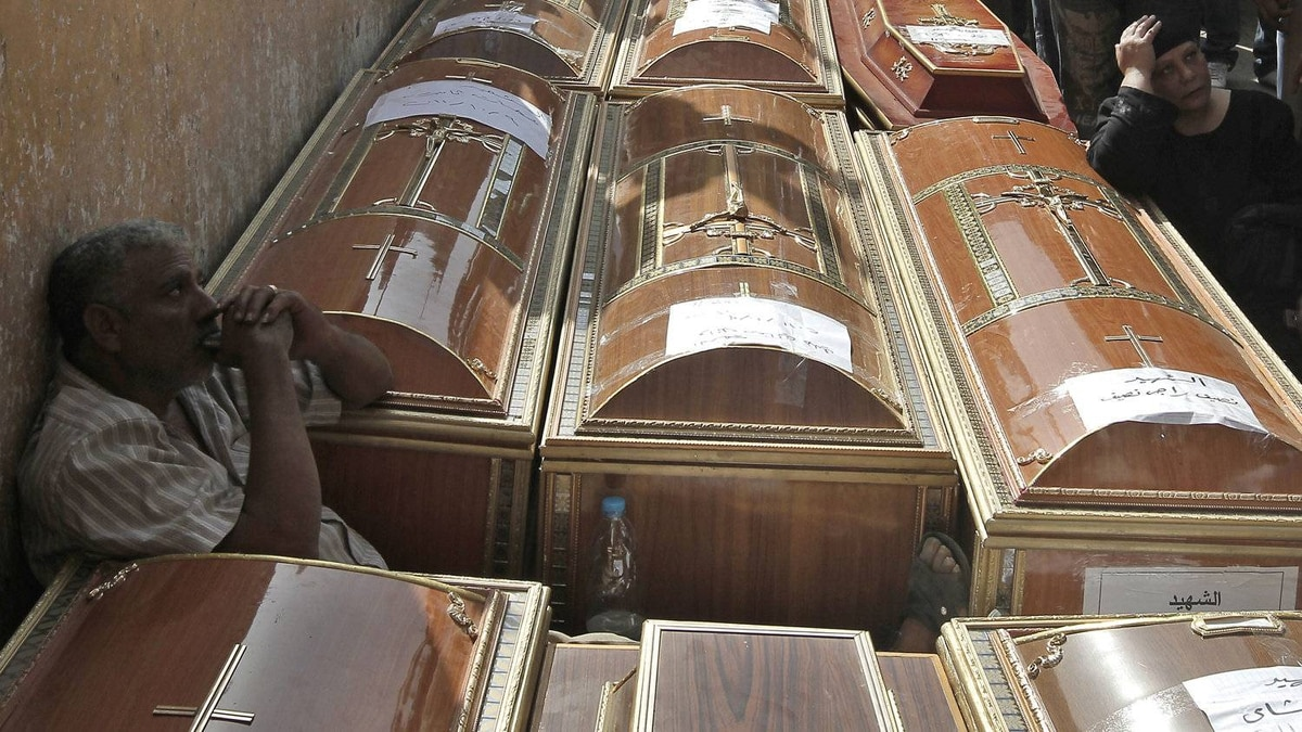 An Egyptian man sits in between coffins as he mourns some of the 24 Coptic Christians killed during over night clashes with Egyptian security forces prior to their funeral procession from the Coptic Hospital in Cairo on October 10, 2011