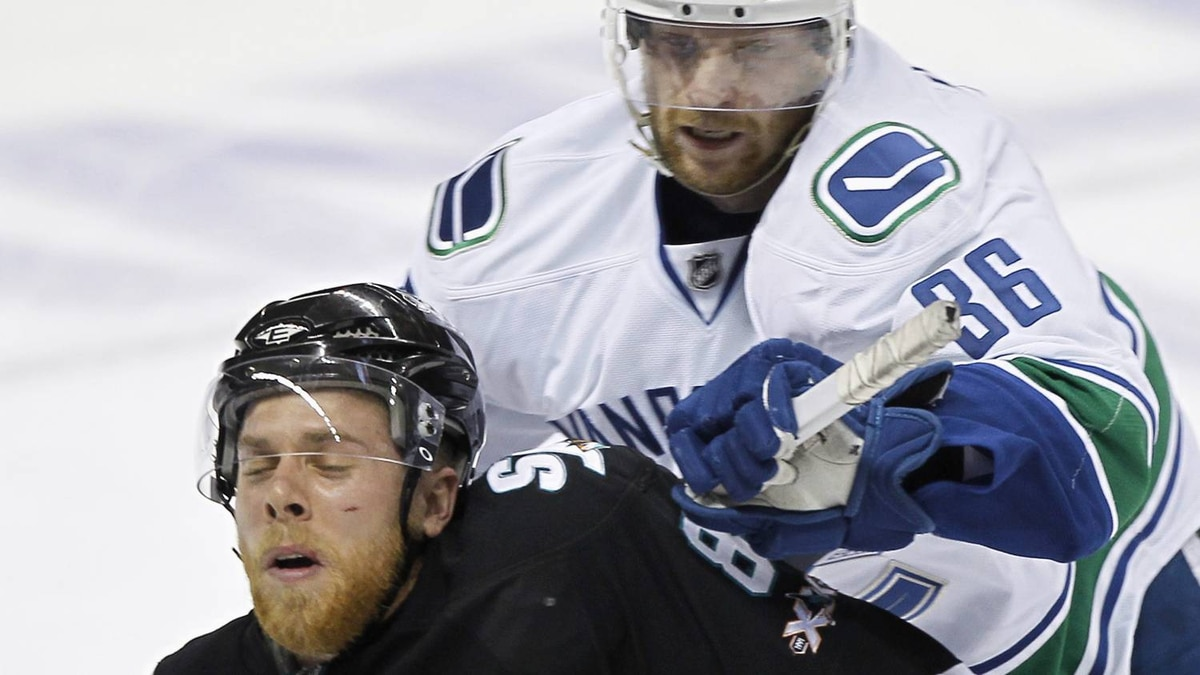 Vancouver Canucks' Jannik Hansen (R) pushed San Jose Sharks'Joe Pavelski from behind during the first period . REUTERS/Mike Blake
