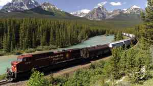 A Canadian Pacific Railway)freight train runs along the Bow River and distant Rocky Mountains on the CP main line near Lake Louise, Alta.