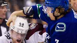 The Vancouver Canucks' David Booth tries to get the helmet off the head of the Colorado Avalanche's Mark Olver.