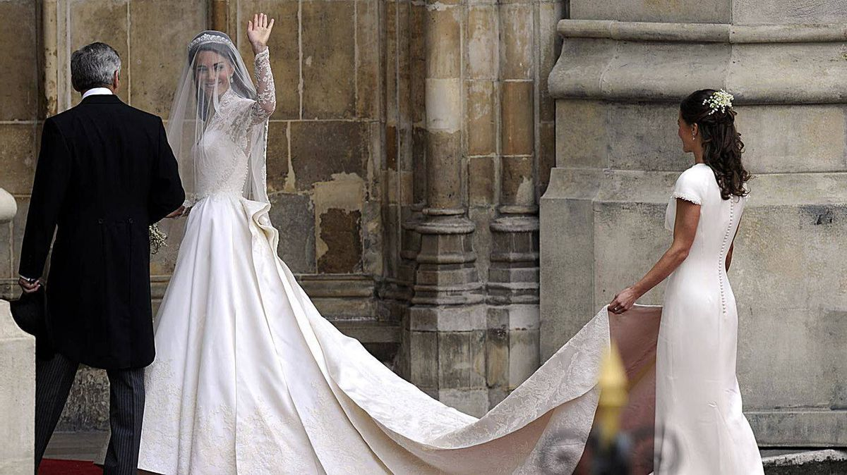 Kate Middleton waves as she arrives with her father Michael Middleton and her sister Philippa Middleton to the West Door of Westminster Abbey in London for her wedding to Britain's Prince William, on April 29, 2011.