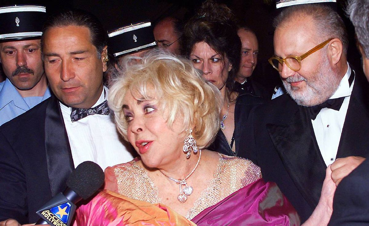 Elizabeth Taylor accompanied by Italian designer Gianfranco Ferre, right, arrives for the American Foundation for AIDS Research benefit party in Mougins, near Cannes, May 20, 1999.