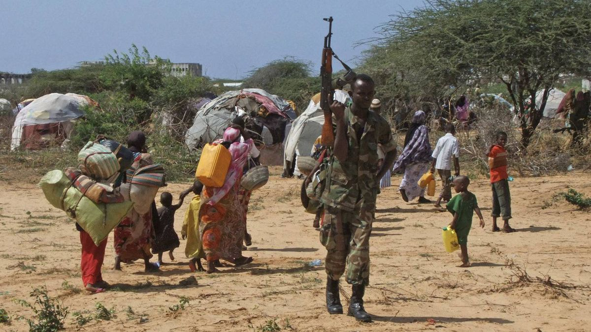 A Somali government soldier stands guard as refugees from the drought-ravaged southern part of the country make their way to a new camp in southern Mogadishu's Hosh neighborhood on Tuesday, July 12, 2011.