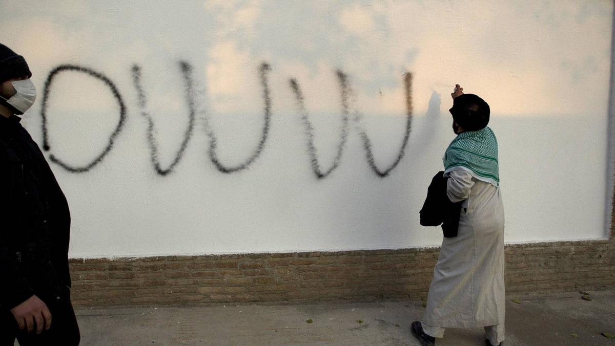 A cleric spray paints graffiti inside the British embassy compound in Tehran.