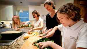 Beth Foster (second from left) and Lesley Fellows (second from right )with their children Claire on the left and Caleb, prepare dinner at home in Montreal Thursday, Sept. 29, 2011.