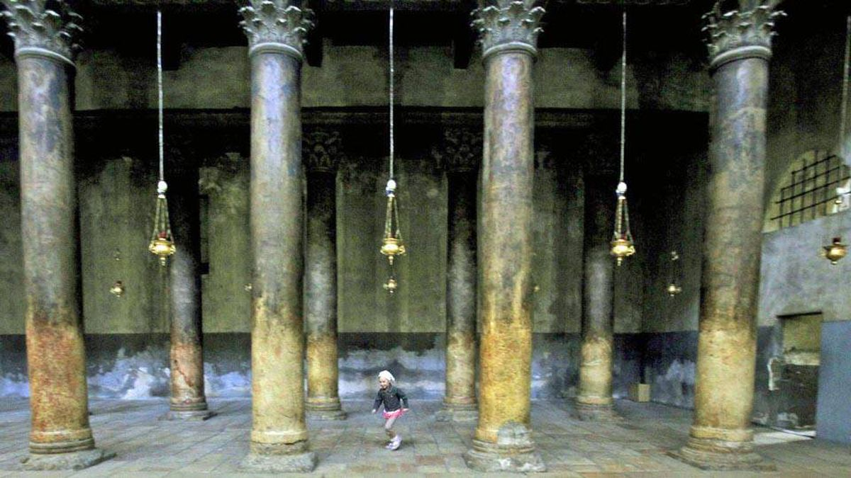 A girl runs between the poles of the Church of the Nativity, traditionally believed by many to be the birthplace of Jesus Christ, in the West Bank town of Bethlehem, Tuesday, May 5, 2009.