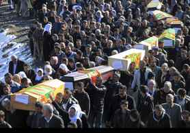 People carry the coffins of victims as thousands of mourners gathered in Gulyazi village, southeast Turkey for the funerals of 35 Kurdish civilians who were killed in a botched raid by Turkish military jets that mistook the group for Kurdish rebels based in Iraq.