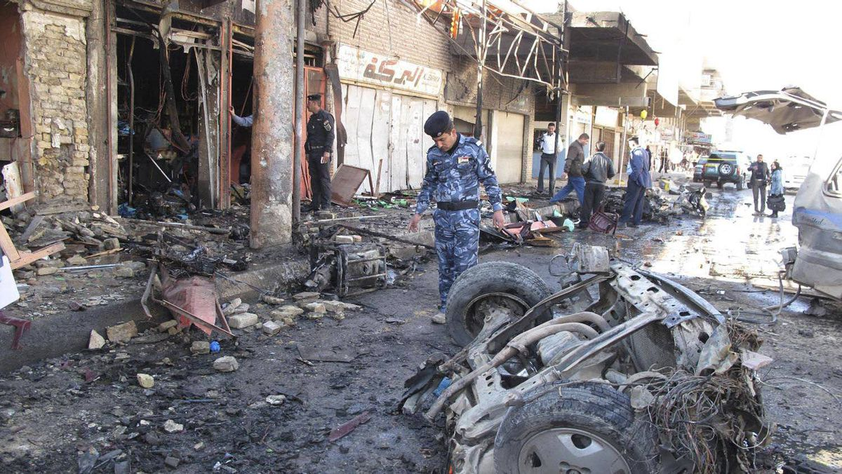 Iraqi security forces inspect the site of a bomb attack in Hilla, 100 kilometres south of Baghdad, on March 20, 2012.
