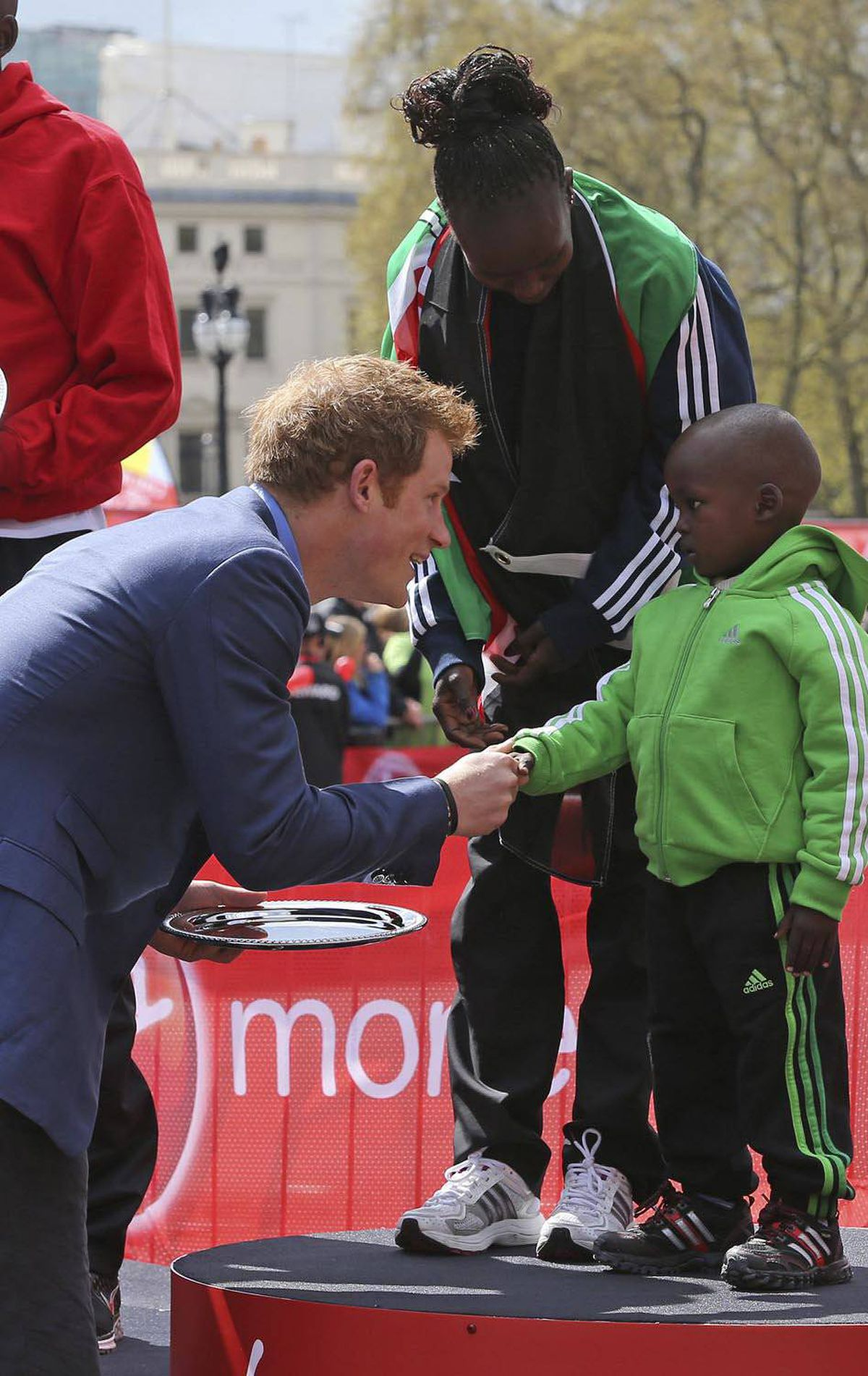 KID-FRIENDLY Prince Harrypresents a trophy to Gerard, son of Kenya's Mary Keitany, the winner of the Women's London Marathon in London April 22, 2012.