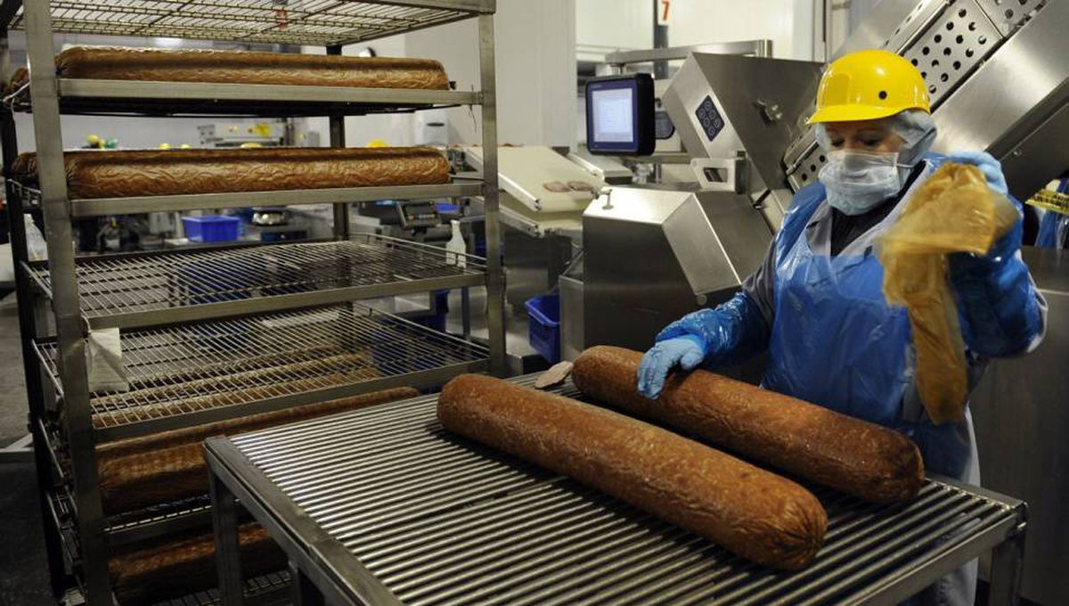 The production area at a Maple Leaf Foods plant. Here, a worker prepares large rolls of bologna for automated slicing.