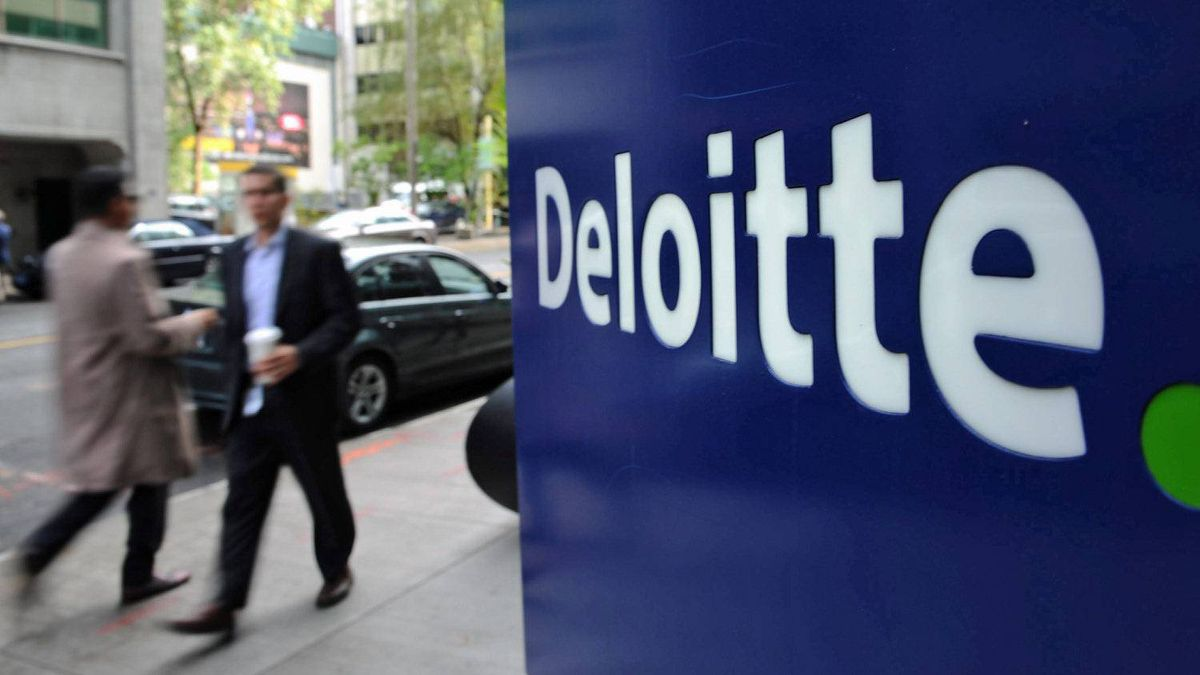 Pedestrians walk past a Deloitte sign in downtown Ottawa on Sept. 20, 2011. The consulting firm was hired on a $20-million contract to advise the Conservative government on how to cut costs.
