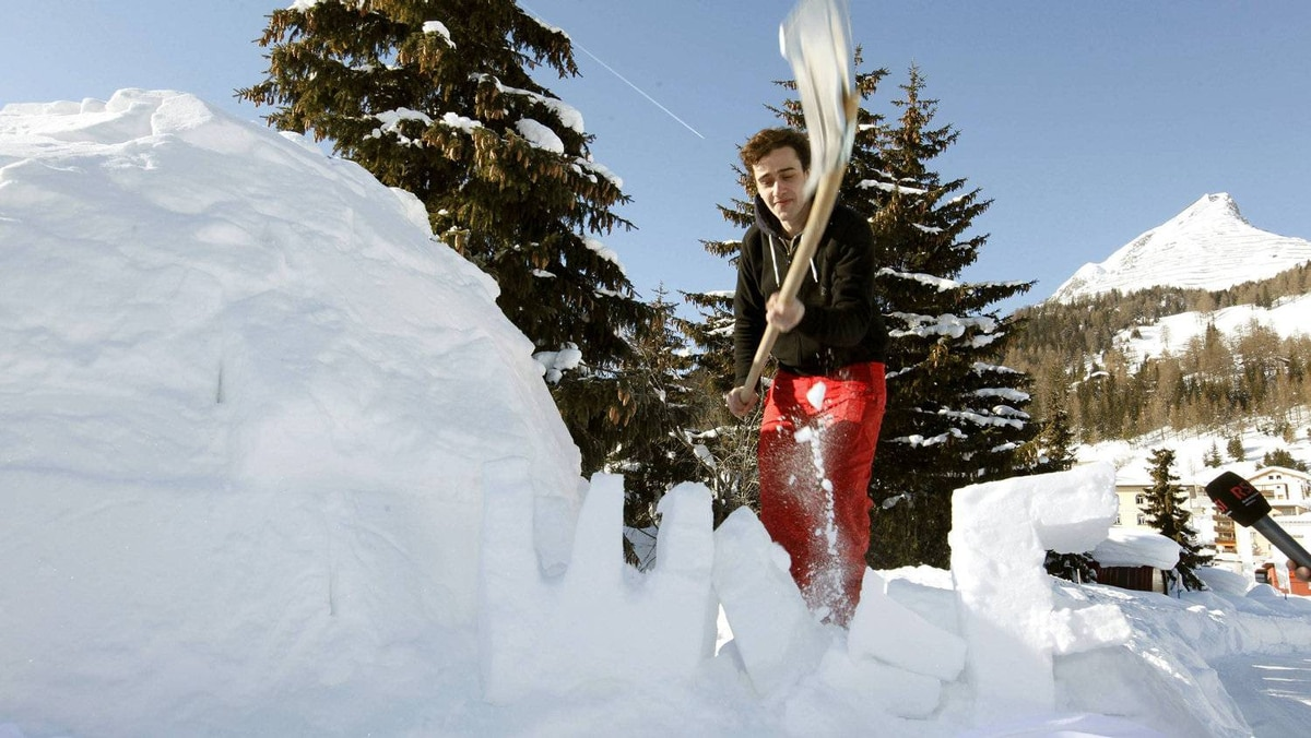 David Roth, president of the youth wing of the Swiss Social Democrat Party, uses a shovel to destroy the snow-built letters WEF beside the first igloo of the Occupy WEF movement.