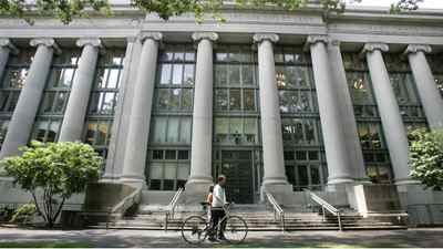 A bicyclist walks by Langdell Hall, the Harvard Law Library, on the campus of the Harvard Law School in Cambridge, Mass., Monday, Aug. 1, 2005. Black-robed for two centuries, the Supreme Court justices could be sporting a new color next term: crimson. That would be to honor Harvard Law School, which if John Roberts is confirmed, could make an unprecedented boast: five of its graduates serving on the high court simultaneously. A sixth justice, Ruth Bader Ginsberg, attended Harvard Law but finished her degree at Columbia. (AP Photo/Charles Krupa)