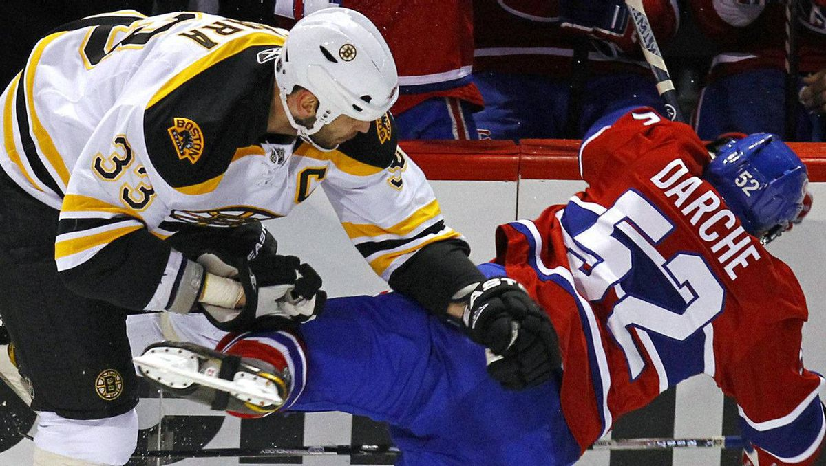 Boston Bruins defenseman Zdeno Chara (33) collides with Montreal Canadiens left wing Mathieu Darche (52) during the first period in Game 3 of their NHL Eastern Conference quarter-final hockey game in Montreal April 18, 2011. REUTERS/Shaun Best