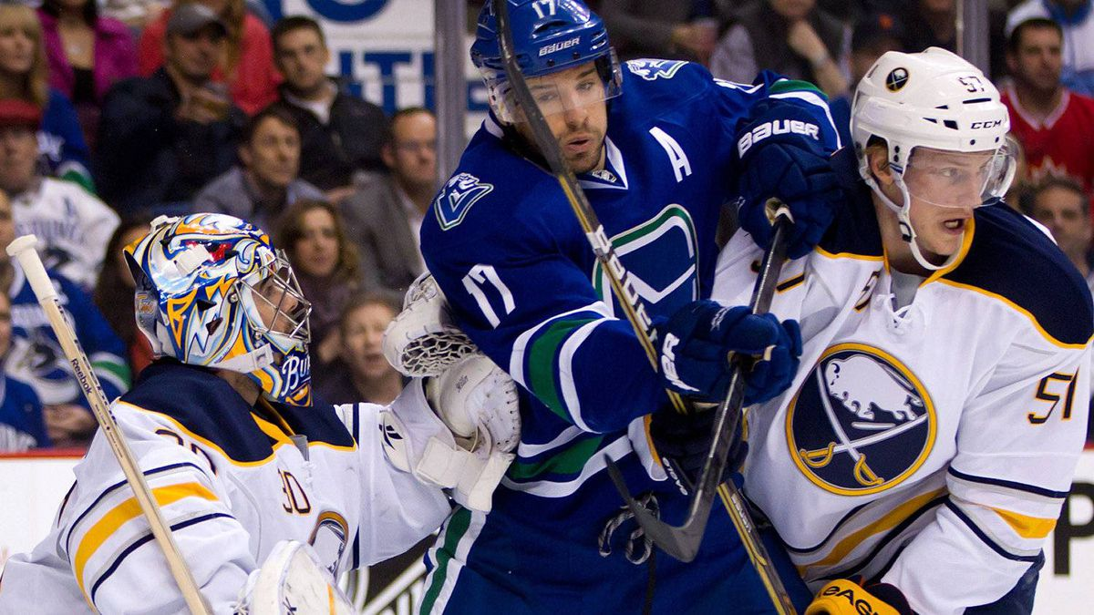 Vancouver Canucks' Ryan Kesler, centre, is checked by Buffalo Sabres' Tyler Myers, right, in front of goalie Ryan Miller during the first period of an NHL hockey game in Vancouver, B.C., on Saturday March 3, 2012. THE CANADIAN PRESS/Darryl Dyck