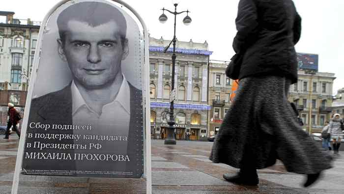A woman in St. Petersburg passes a board Jan. 11 displaying a portrait of Russian billionaire Mikhail Prokhorov, appealing for his supporters' signatures. Two million are needed for the registration of a presidential candidate,