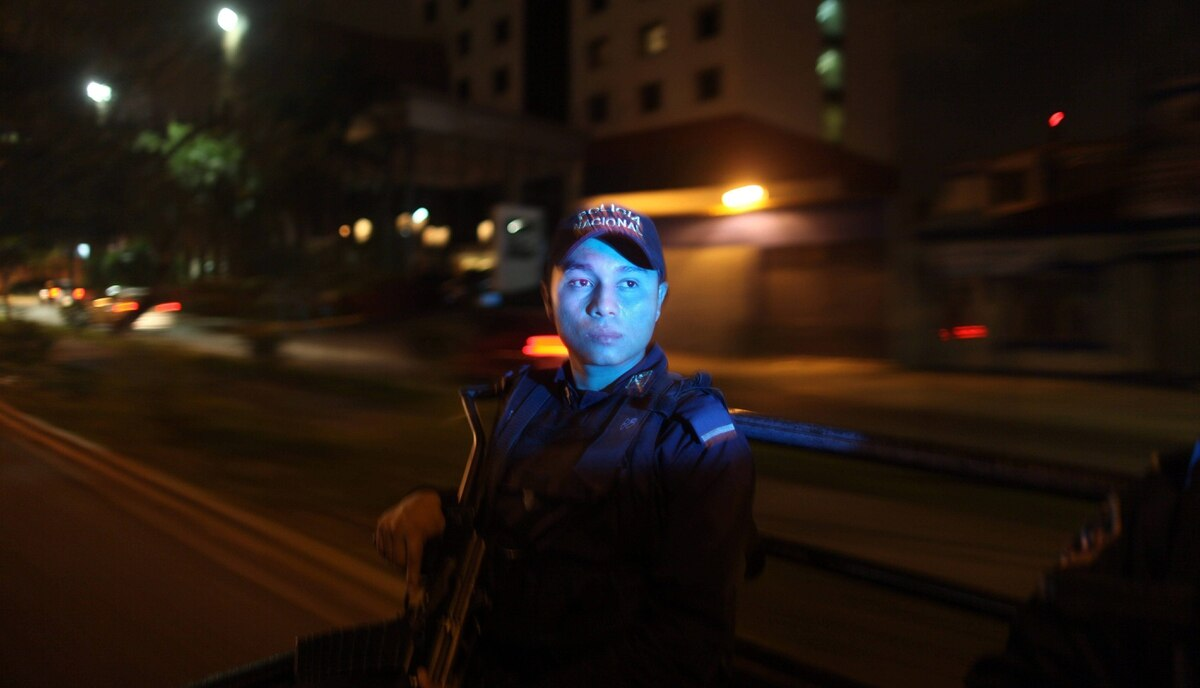 A police officer patrols in the back of a police truck in San Pedro Sula, Honduras March 8, 2012. A wave of violence has made Honduras among the most dangerous places on Earth, with a homicide rate roughly 20 times that of the U.S. rate, according to a 2011 United Nations report.