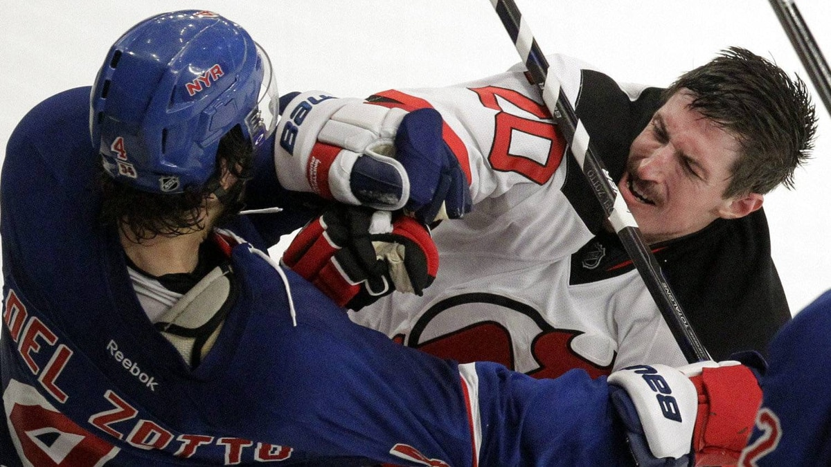 New Jersey Devils' Ryan Carter, center, swings at New York Rangers' Michael Del Zotto, left, as Artem Anisimov (42) watches during the second period of Game 5 of an NHL hockey Stanley Cup Eastern Conference final playoff series, Wednesday, May 23, 2012, in New York.