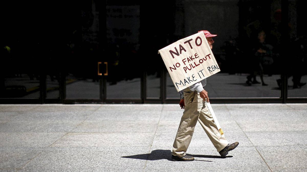 A protester holds a sign as he marches during a demonstration leading up to the NATO Summit in Chicago May 18, 2012. The Summit runs from May 20-21.