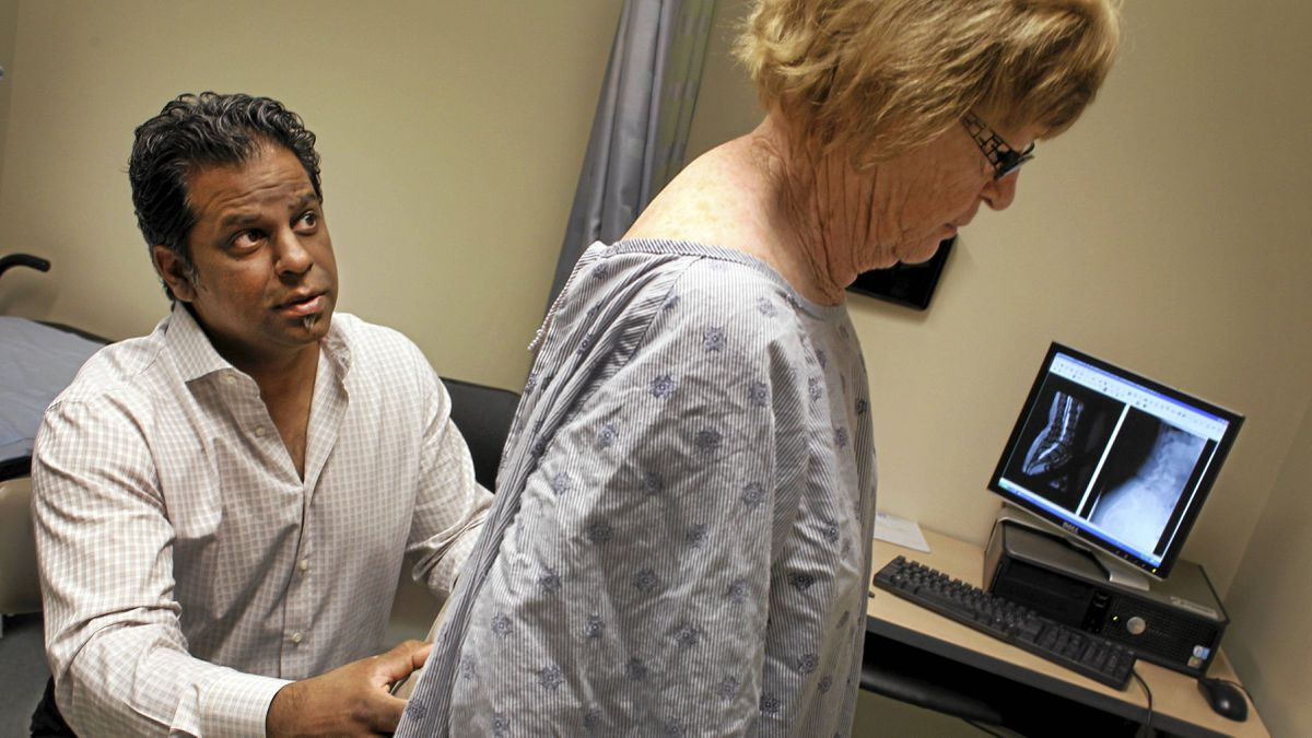 Dr. Raja Rampersaud examines and consults with his patient, Barbara Gamsby at Toronto Western Hospital on May 9, 2011.