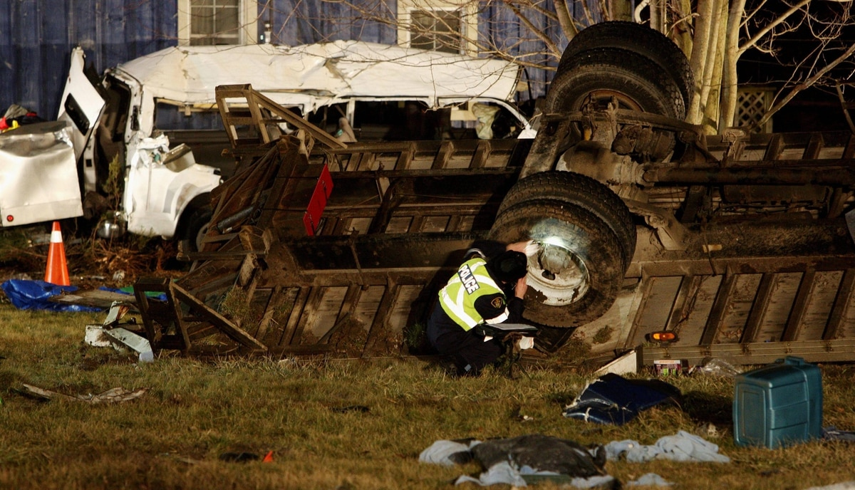 Ontario Provincial Police and emergency crews investigate a multiple fatal motor vehicle accident near Hampstead, Ontario, Monday, February 6, 2012. Police say 11 people died in the crash.