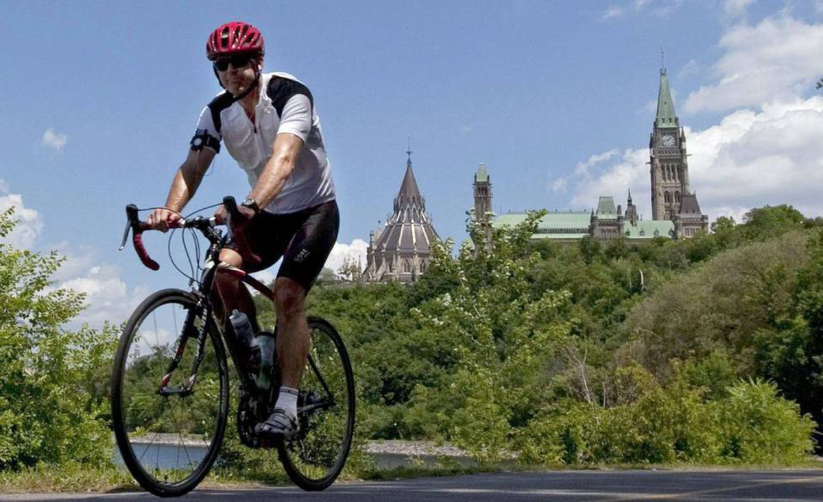 A cyclist rides with a helmet near Parliament Hill on July 8, 2010. Provincial governments should force anyone riding a bicycle to wear a helmet, says the co-author of a new report that found helmet use varies greatly across Canada.