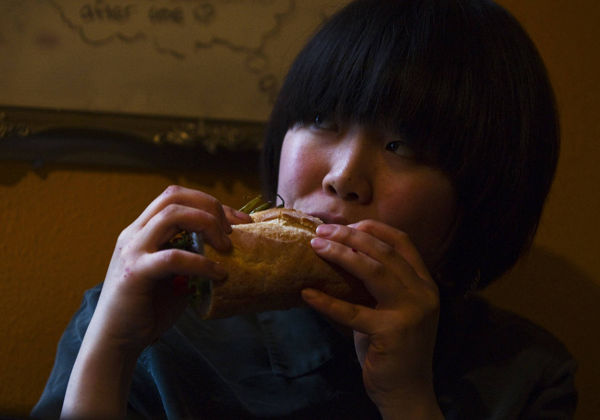 Ritsuko Hatanaka, 23, a practising 'freegan', eats a sandwich made from scavenged food in Vancouver.