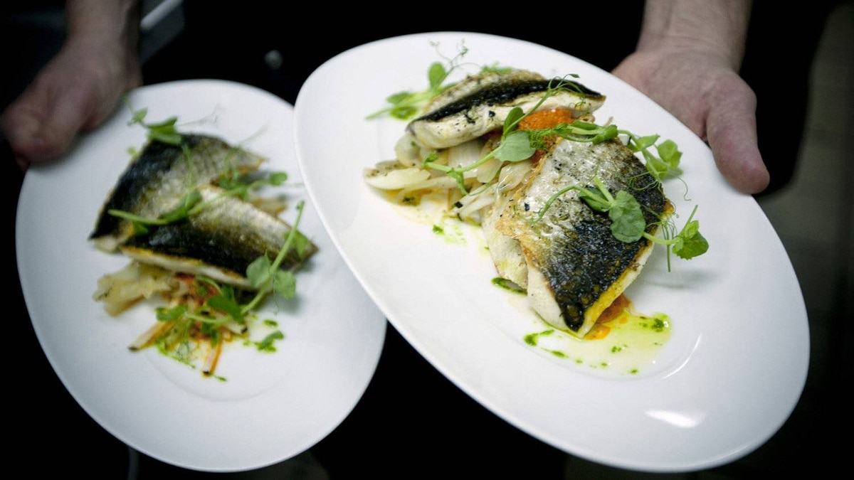 In this Wednesday, April 4, 2012 photo, Israeli chef Noam Dekkers of Liliyot restaurant holds two versions of a fish dish, one kosher for Passover and another served on a piece of bread, right, at a restaurant in Tel Aviv, Israel.