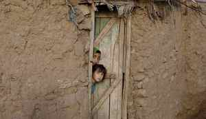 Afghan refugee girls peek out of a door of their house, in a slum area on the outskirts of Islamabad, Pakistan, Sunday, Oct. 9, 2011. (AP Photo/Muhammed Muheisen)