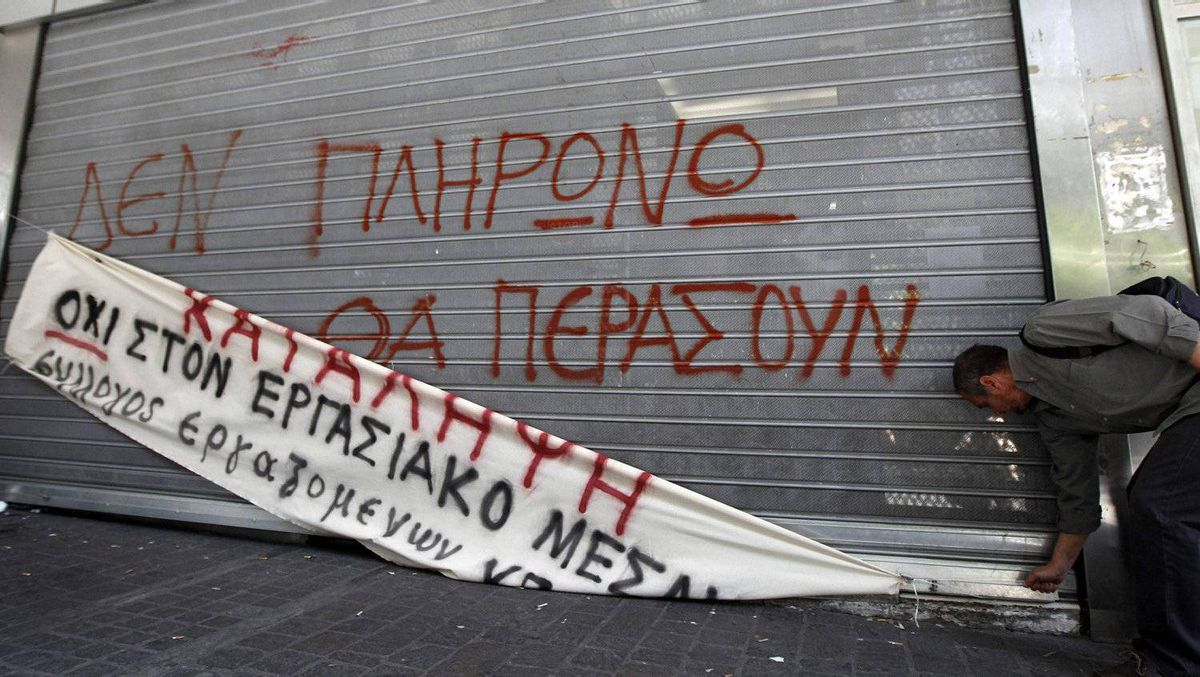 """A protester places a banner in front of the closed entrance of the Finance Ministry during a blockade by employees in Athens on Sept. 29, 2011. Greek civil servants blocked the doors of government ministries on Thursday in protest against austerity ahead of the start of talks with the EU and IMF on the delivery of an aid tranche Athens needs to avoid running out of cash next month. The fence reads: """"I won't pay"""" and the banner reads: """"Occupation""""."""