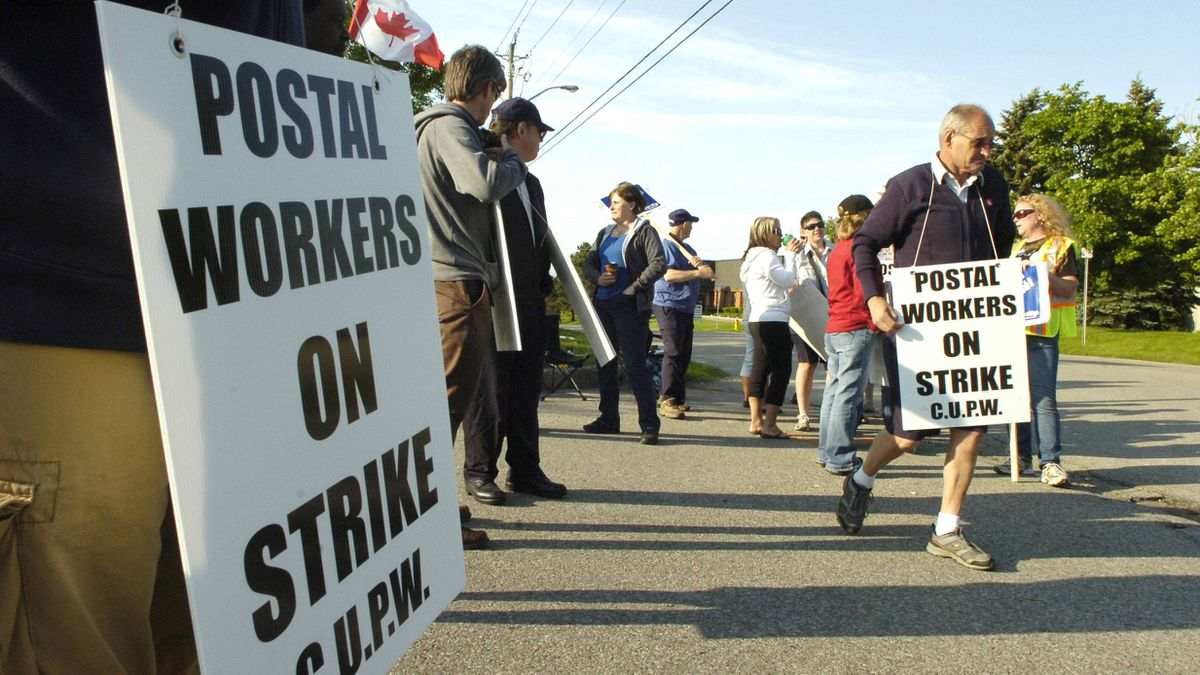 Postal workesr walk a picket line at the Canada Post facility in Kitchener, Ont., on Friday, June 10, 2011.