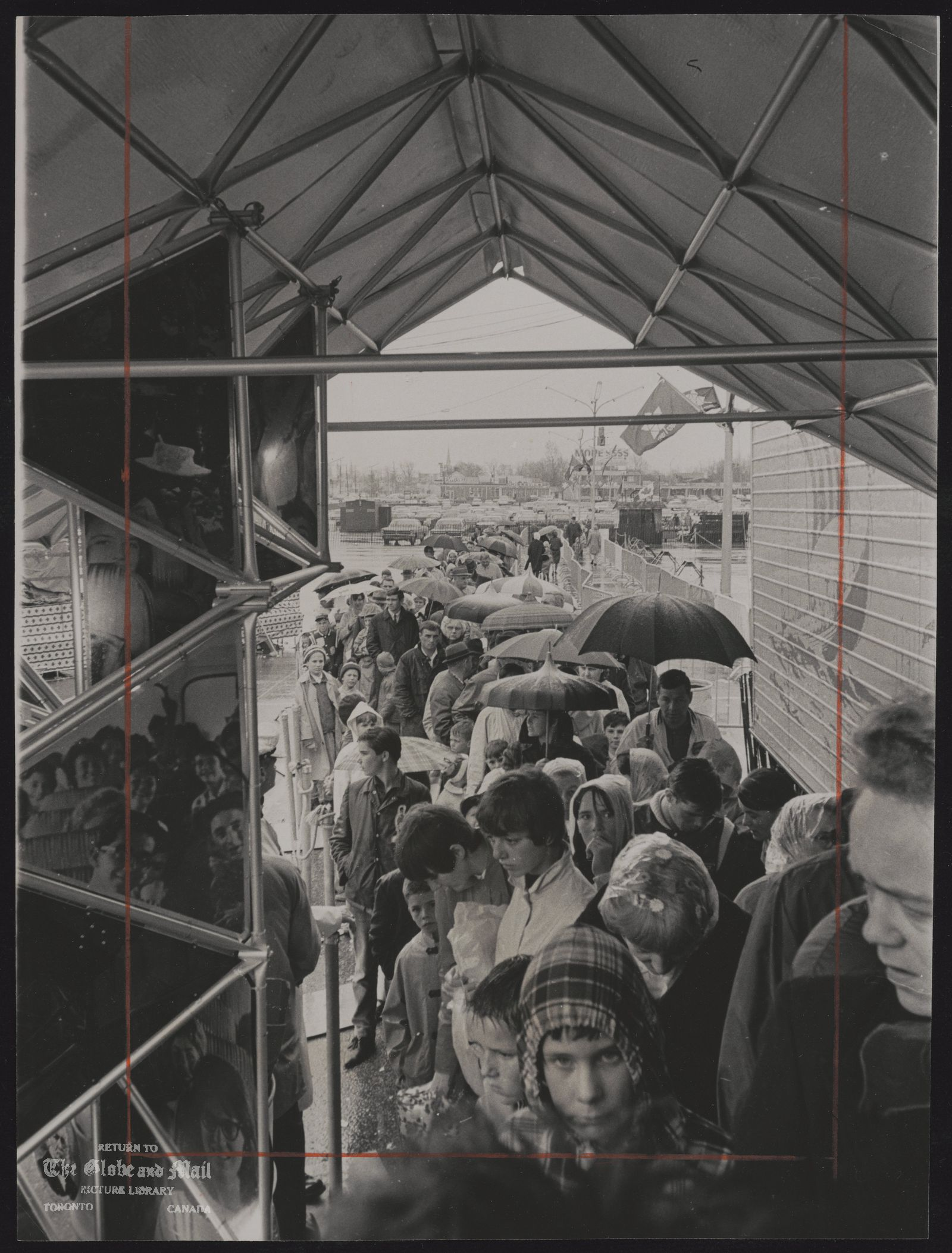 The notes transcribed from the back of this photograph are as follows: CANADA Centennial Caravans Line up for Confederation Caravan. Umbrella-armed visitors line up in the rain to tour the Confederation caravan in Richmond Hill. The caravan stays there until tomorrow before moving to Newmarket.