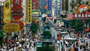 Shoppers crowd under huge signs along Shanghai's bustling Nanjing Road August 3, 2001.