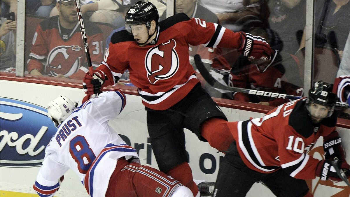 New Jersey Devils' Anton Volchenkov (C) checks New York Rangers' Brandon Prust (L) with teammate New Jersey Devils' Peter Harrold during the first in Game 3 of their NHL Eastern Conference Final hockey playoff game in Newark, New Jersey, May 19, 2012.