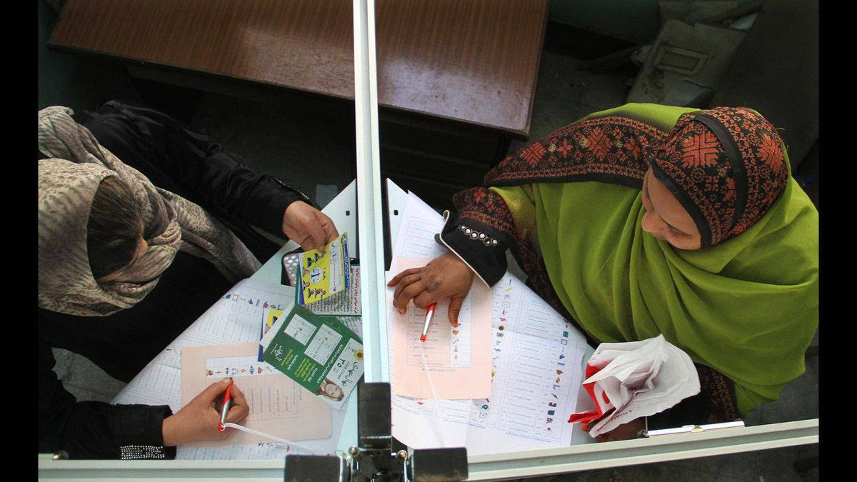 Two Egyptian women are seen in voting booths cast their votes on the second day of parliamentary elections in Cairo, Egypt, Tuesday, Nov. 29, 2011.