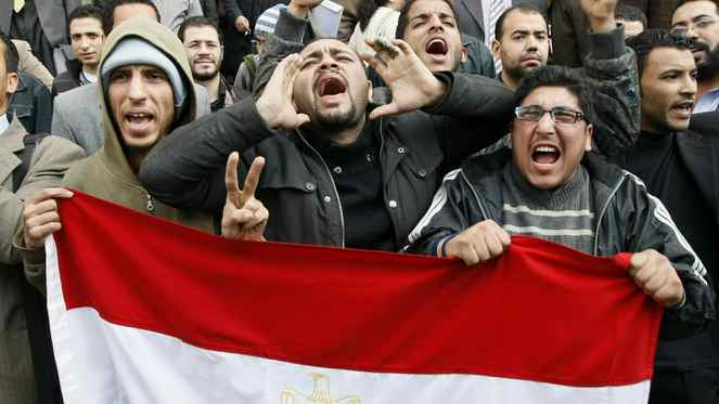 Egyptian demonstrators hold their national flag during demonstration in Cairo on Jan. 27, 2011 demanding the ouster of President Hosni Mubarak.