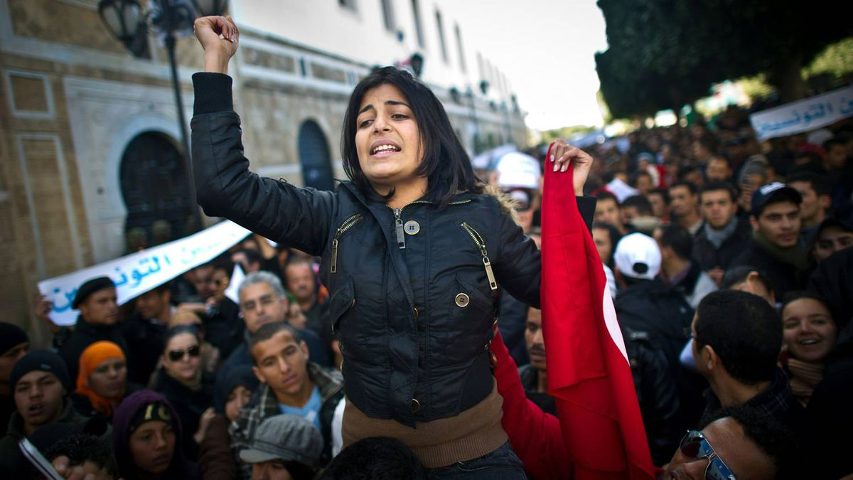 A woman raises her fist during a demonstration calling on the new government to quit, on Bourguiba avenue in central Tunis on January 22, 2011. Thousands of people rallied in Tunisia today as the prime minister said he would resign only once the first democratic vote since independence has been held.