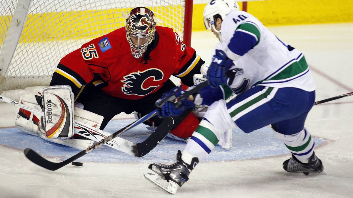 Vancouver Canucks' Maxim Lapierre, right, tries to get the puck past Calgary Flames goalie Henrik Karlsson, from Sweden, during first period NHL hockey action in Calgary, Alta., Saturday, April 9, 2011. The Canucks won 3-2 in overtime. THE CANADIAN PRESS/Jeff McIntosh