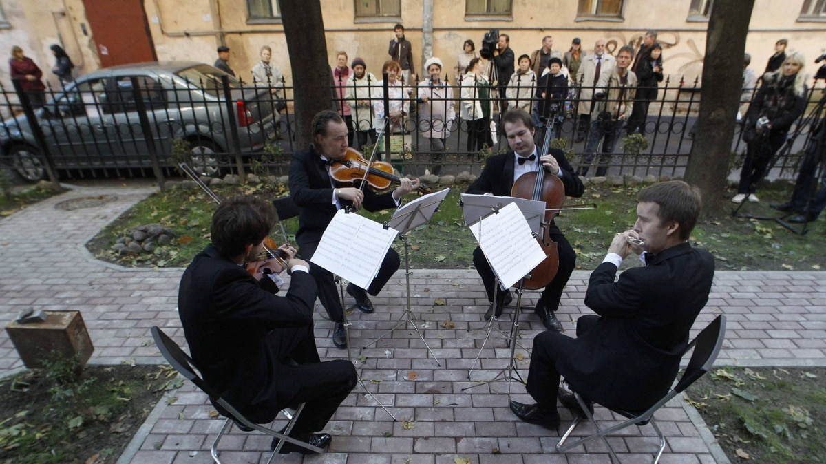 "Classical quartet ""Concerteum"" perform in an apartment block courtyard as they start the programme of ""Musical wanderers"" on the Vasilyevsky Island in St. Petersburg, September 19, 2011."
