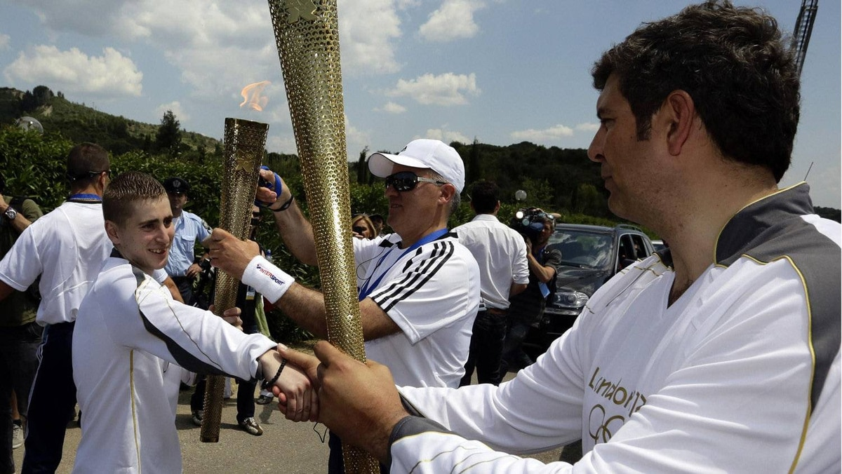 Alexander Loukos (L), British boxer of Greek descent, prepares to light the torch held by Spyros Philipas (R), president and chief executive of BMW Hellas, during the Olympic torch relay at the site of ancient Olympia in Greece May 10, 2012.