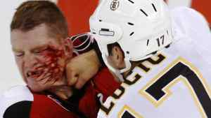 Ottawa Senators' Chris Neil (24) takes a punch in the face from Boston Bruins' Milan Lucic during first period NHL preseason hockey action in Ottawa Friday September 25, 2009. THE CANADIANPRESS/Fred Chartrand